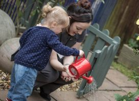 poplars day nurseries offer individual care, child playing with watering can