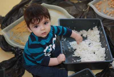 individual childcare toddler playing with rice