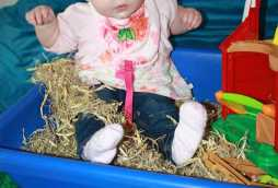 babies day care, toddler playing with hay