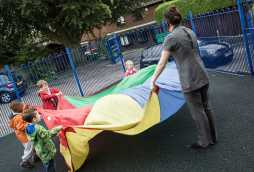 nursery school and childcare for children in woodthorpe playing with multi-coloured parachute