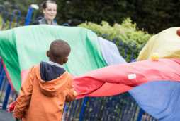 nursery activities children playing with parachute fabric