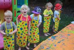 pre-school day nursery children hand painting outside